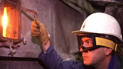 Un homme avec in casque ouvre la trappe d'un fourneau