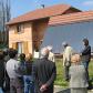 Un groupe de personnes devant un maison qui a beaucoup de panneaux solaires